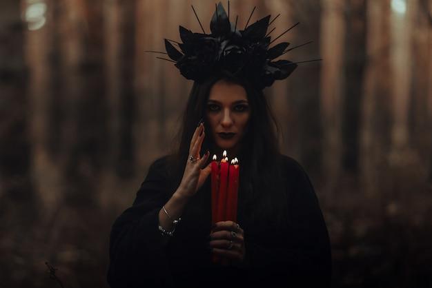 黒いひどい魔女は暗い森の中で彼女の手にろうそくを持っています