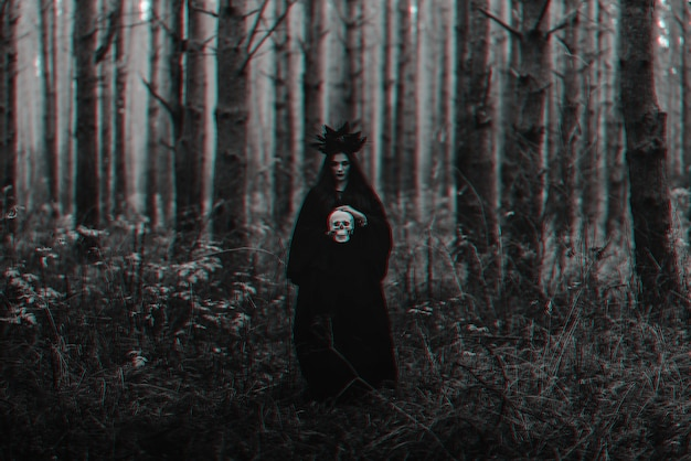 Black terrible witch holds the skull of a dead man in her hands. black and white with 3d glitch virtual reality effect