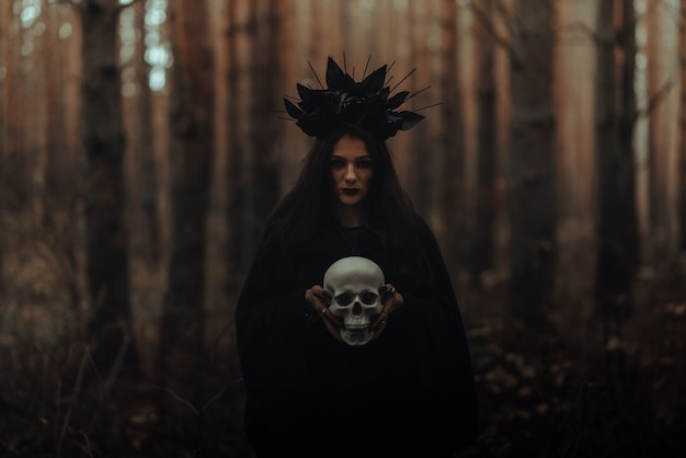 Black terrible witch holds the skull of a dead man in her hands in a dark forest
