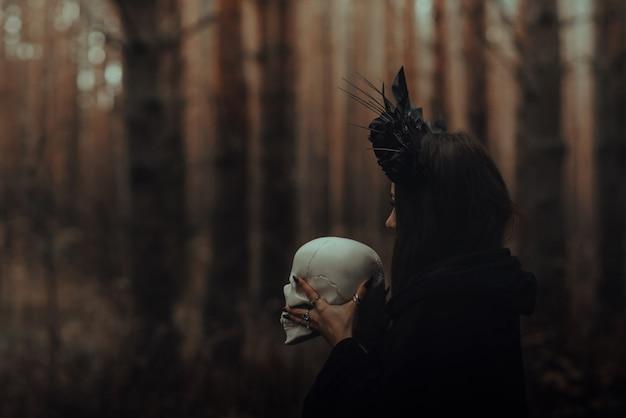 죽은 사람의 손에 해골이 달린 검은 끔찍한 마녀가 숲에서 신비로운 신비로운 의식을 수행합니다.