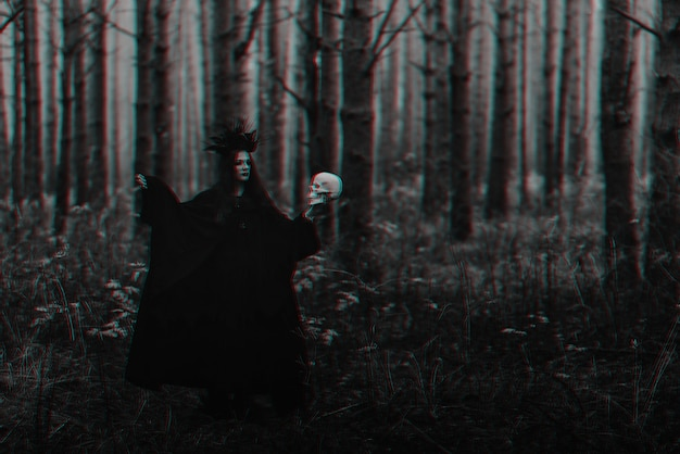 Black terrible witch with a skull in the hands of a dead man performs an occult mystical ritual. black and white with 3d glitch virtual reality effect