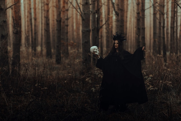 Black terrible witch with a skull in the hands of a dead man performs an occult mystical ritual in the forest