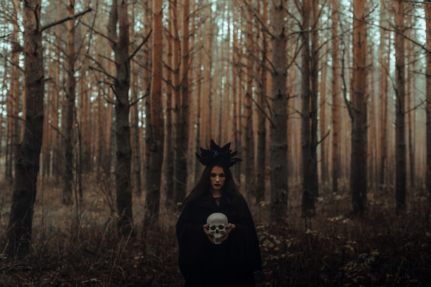 Black terrible witch with a skull in the hands of a dead man in the woods
