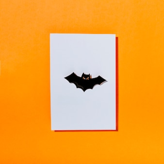 Black terrifying bat on piece of white paper