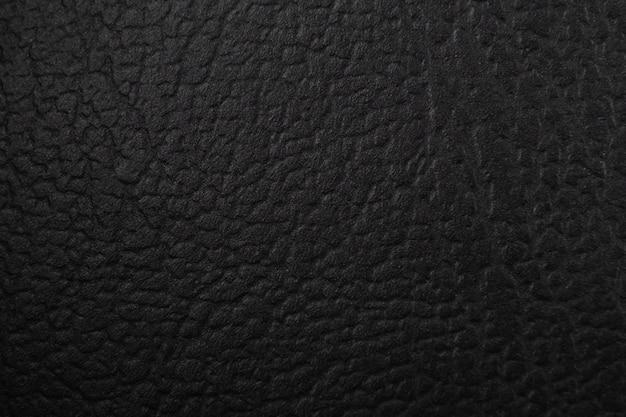 Black textured leather texture in dark.