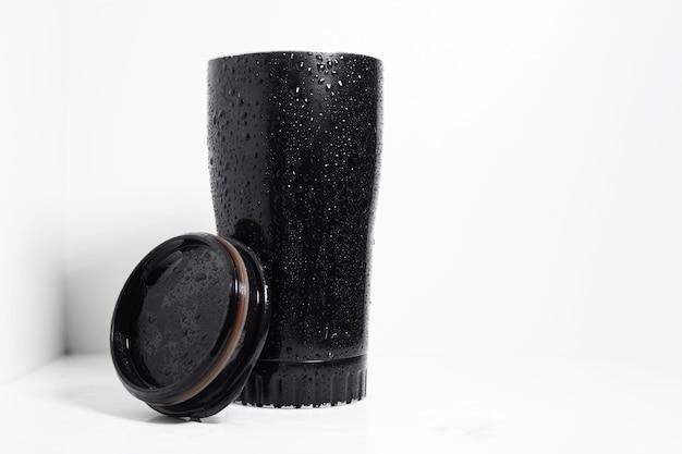 Black thermal mug for coffee on white.