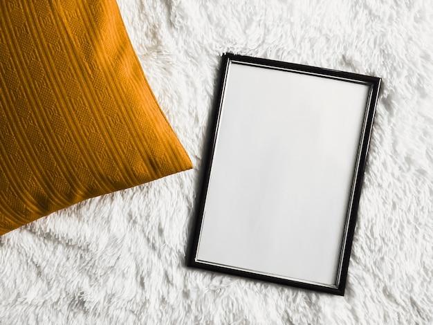 ポスター写真プリントモックアップ金色のクッション枕として空白のコピースペースと黒の薄い木製フレームと...