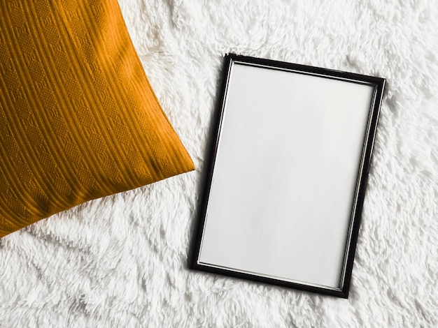 Black thin wooden frame with blank copyspace as poster photo print mockup golden cushion pillow and ...