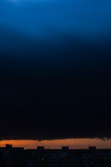 日没時の黒い雷雲。明るいオレンジ色の夕日と暗い雲。嵐の空