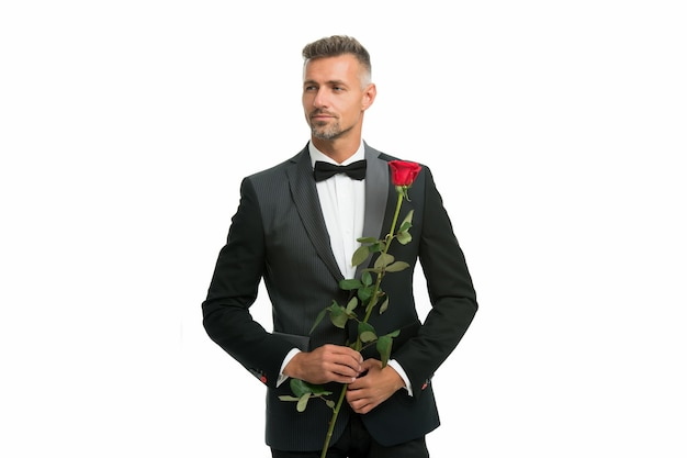 夜のイベントの黒のネクタイドレスコード。バラの花を持つタキシード男。幸せなバレンタインデー。特別な行事。男性のフォーマルな服装。ハンサムな男黒タックススーツ。ロマンチックなデートのセクシーな男。