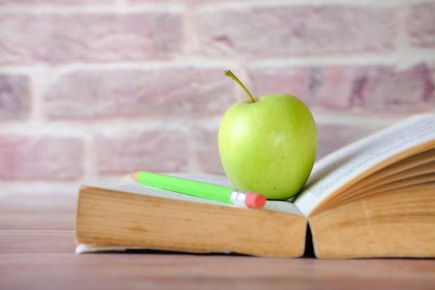 테이블에 펼친 책에 사과와 학교 개념 블랙,