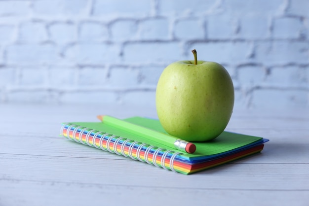 Черный в школу концепции с яблоком на блокноте на столе.