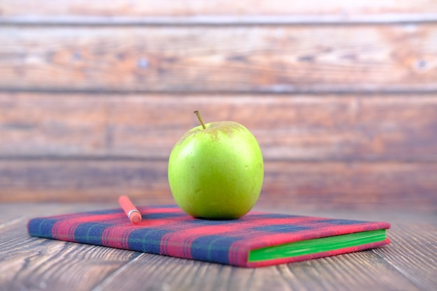 テーブルの上のメモ帳にリンゴと学校のコンセプトに黒
