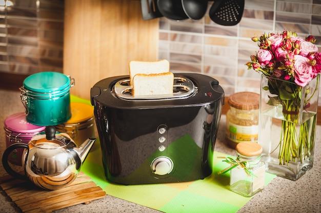 식탁에 빵 조각으로 검은 토스터기