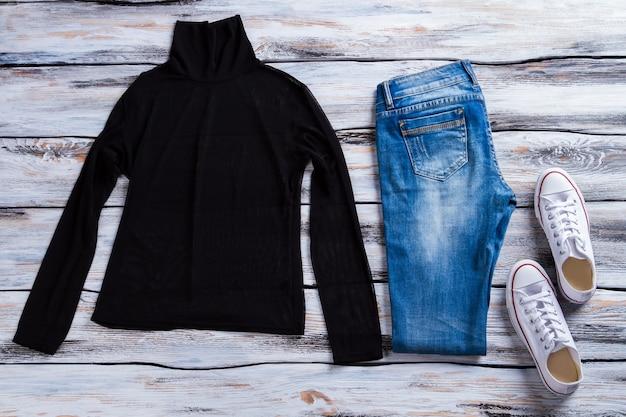 청바지와 흰색 캔버스 신발이있는 검은 색 탑과 하이 칼라 탑 여성 의류가있는 바지 복장 ...
