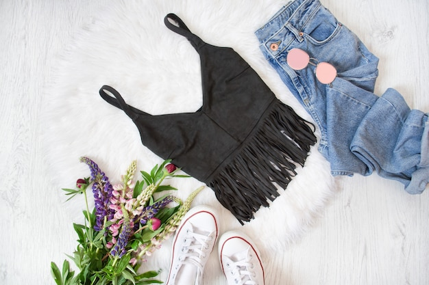 Black top with fringe, blue jeans, white sneakers. bouquet of wild flowers. fashionable concept