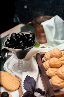 Black traditional walnut confiture in a glass jar with butter cookies on a wooden board