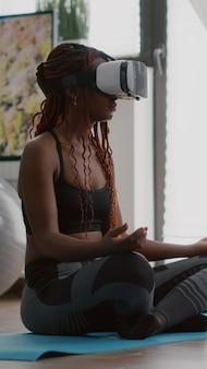 ヨガマップに座っている間バーチャルリアリティヘッドセットを身に着けている黒人トレーナーの女性