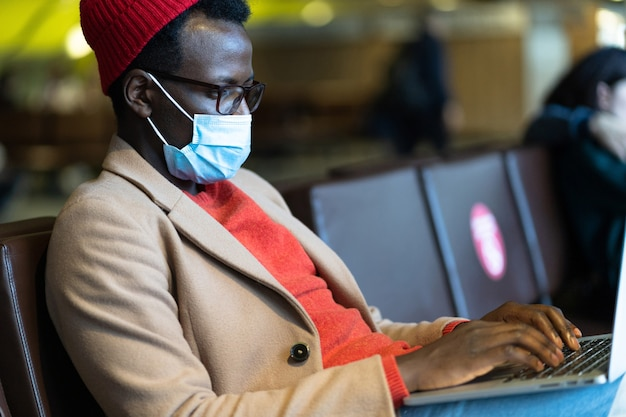 Black traveler man wear face protective mask, sitting in airport, works remotely on laptop. covid-19