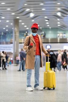 Темнокожий путешественник с чемоданом стоит в аэропорту, используя мобильный телефон в маске для лица