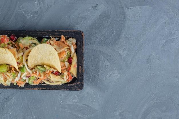Черный поднос смешанного овощного салата, украшенного картофельными чипсами на мраморном фоне.