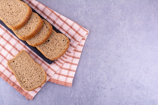 Black tray of sliced brown bread on a folded towel on marble surface