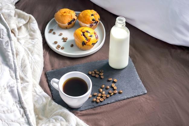 朝食用のマフィンケーキとベッドの上のボトルにコーヒーと牛乳のカップが入った黒いトレイ。