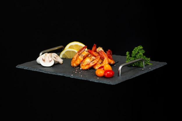 黒の野菜とスタイリッシュなおいしいエビと黒のトレイ