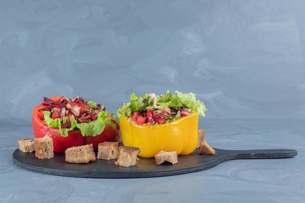 야채 샐러드의 두 부분과 대리석 배경에 말린 빵 껍질이있는 검은 색 트레이.