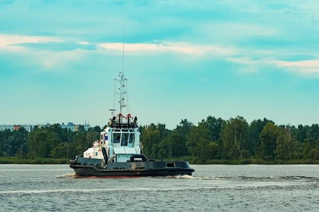 화물 터미널로 이동하는 검은 예인선 배. 산업 서비스