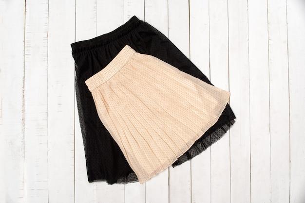 白い木製の背景に黒のチュールとベージュのスカート。上面図