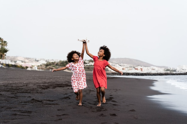 Black twin sisters running on the beach while playing with wood toy airplane - focus on faces