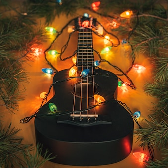 Black ukulele guitar and christmas decorations on the dark background. hawaiian guitar with lighted garland on dark background. new year and christmas music, concept