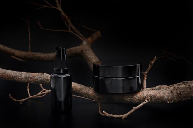 Черная баночка с косметическим кремом и сывороткой с веткой дерева других производителей. презентация продукта по уходу за кожей на черном фоне. элегантный макет. уход за кожей, красота и спа.