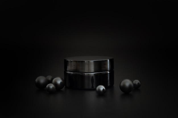 Черная баночка с косметическим кремом других производителей. презентация крема на черном фоне. элегантный макет. уход за кожей, косметический продукт.