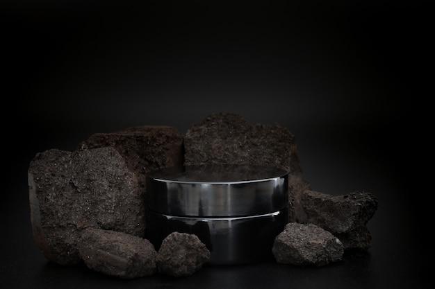Черная баночка с косметическим кремом других производителей. презентация крема с камнями на черном фоне. элегантный макет. уход за кожей, косметический продукт.