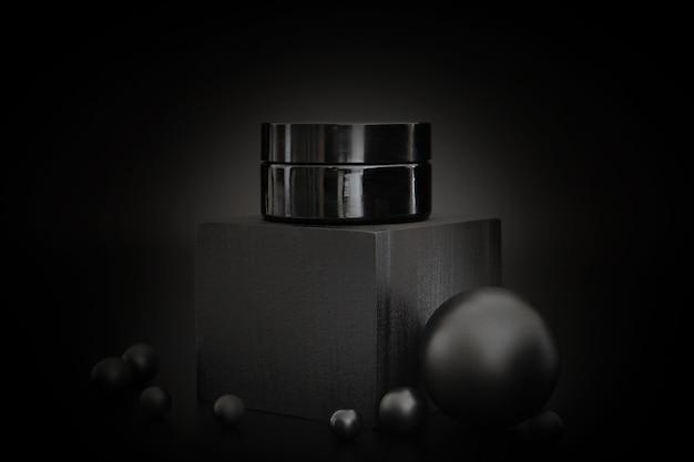 Черная баночка с косметическим кремом других производителей, стоящая на черном подиуме. презентация продукта по уходу за кожей на черном фоне. элегантный макет. уход за кожей, красота и спа.