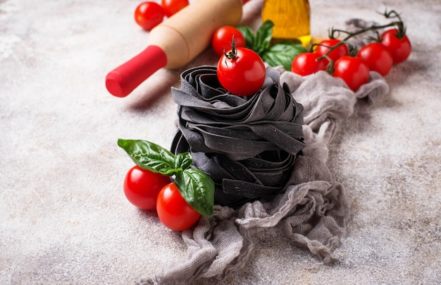 Black uncooked pasta with tomato and basil