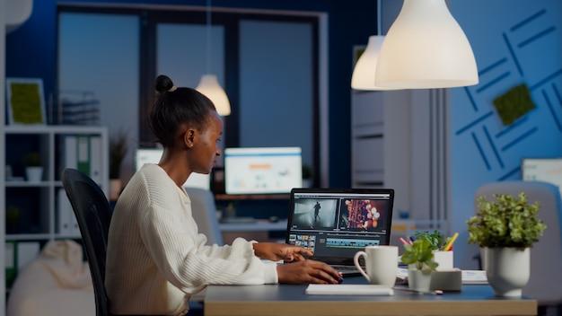 スタートアップの営業所に座っているオーディオフィルムモンタージュを編集する新しいプロジェクトで残業している黒いビデオ編集者。プロのラップトップ、最新技術、ネットワークワイヤレスを使用する女性コンテンツクリエーター