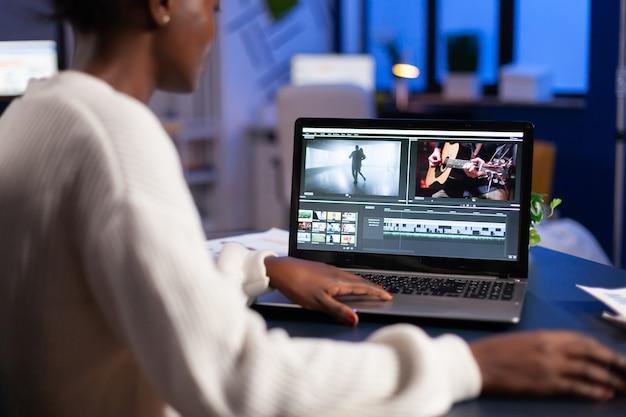 Черный видеоредактор работает сверхурочно над новым проектом, редактирует монтаж аудиозаписи, сидя в офисе стартапа