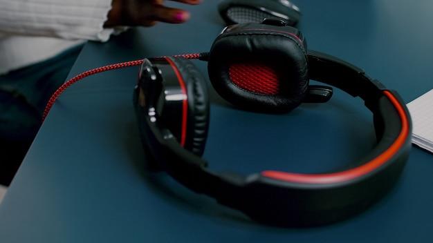 두 개의 모니터가 헤드폰을 끼고 pc에서 푸티지 작업을 하는 검은색 비디오 편집기 아프리카 비디오...