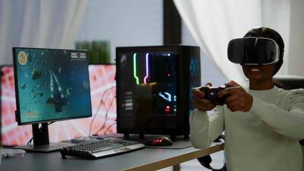 現代のジョイパッドでゲームをプレイするバーチャルリアリティゴーグルを使用して、宇宙シューティングゲームに勝つ黒人のビデオゲーマー女性。強力なコンピューターで新しいグラフィックスを使用してオンラインビデオゲームをストリーミングするプロのゲーマー
