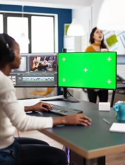 크로마 키가 있는 컴퓨터를 사용하는 흑인 비디오그래퍼, 격리된 디스플레이 편집 비디오 및 오디오 푸티지