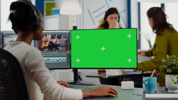 Black videographer using computer with chroma key mock up isolated display editing video and audio f...