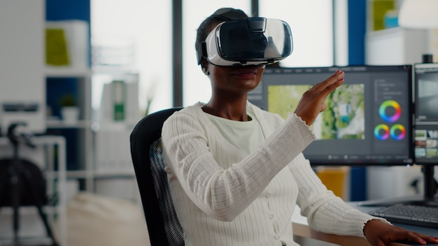 Black videographer wearing vr headset editing project