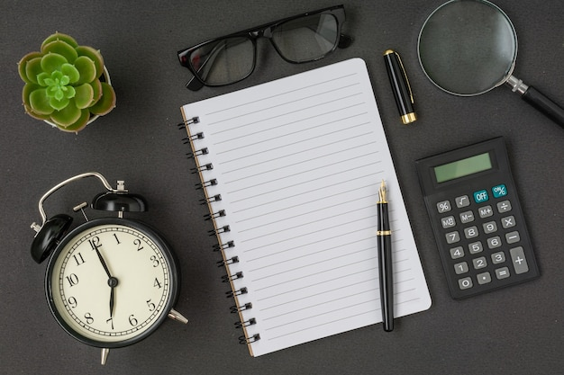 검은색 빈티지 알람 시계 계산기 안경 노트북과 검은색 바탕에 복사 공간이 있는 펜 플랫 레이