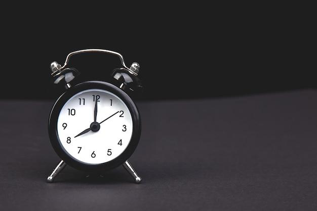 Black vintage alarm clock. eight o'clock.