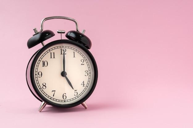 淡いピンクの背景に黒のヴィンテージ目覚まし時計は、5時間の時間を示しています