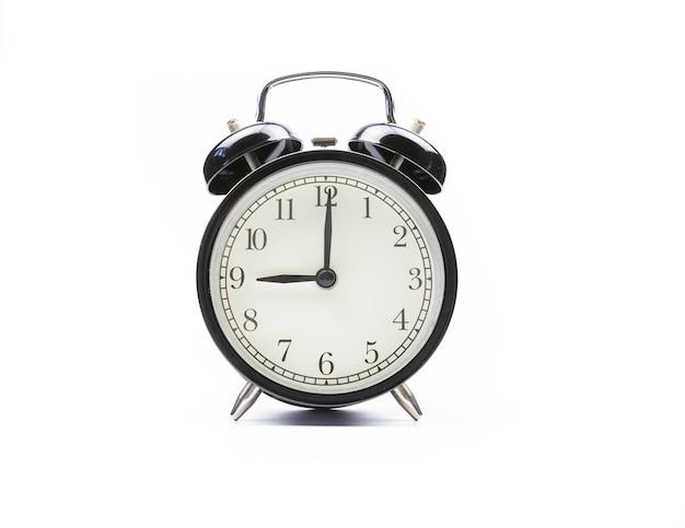 白い背景の上の黒いヴィンテージ目覚まし時計は9時を示しています