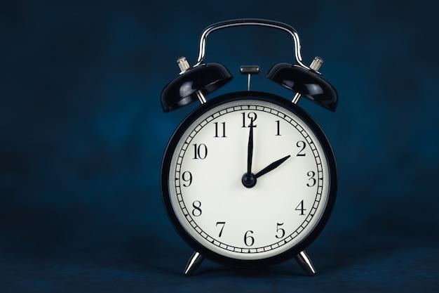 검은색 빈티지 알람 시계는 어두운 배경에서 분리된 2시 방향을 보여줍니다.